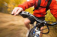 Young man mountain biking during fall near Fallen Leaf Lake, CA.