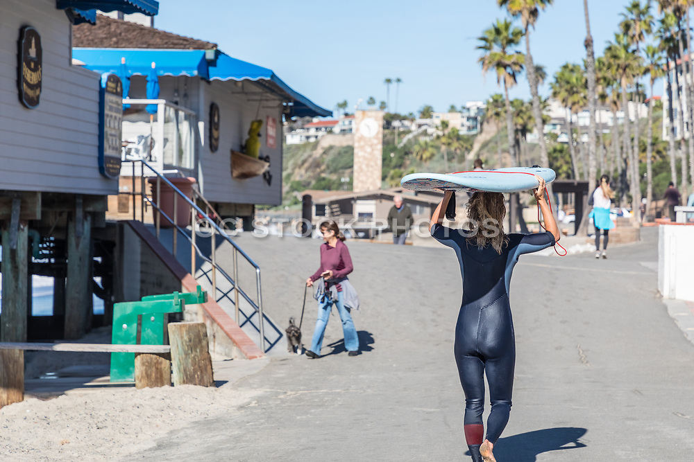 Female Surfer Walking Past Fisherman's Restaurant at the Pier Bowl