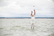 A player takes a catch from the deep outfield during the annual Bramble Bank cricket match in the middle of the sea. The eccentric game involves members of the Royal Southern Yacht Club in Hamble playing against the Island Sailing Club from Cowes on the Brambles, a patch of sand in the Solent, only visible for a few minutes on the spring tide. The teams take turns in winning. This year the Royal Southern team won and hosted dinner at their club house.<br /> Picture date Monday 31st August, 2015.<br /> Picture by Christopher Ison. Contact +447544 044177 chris@christopherison.com