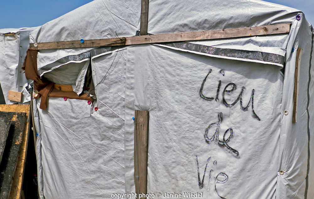 """Lieu de Vie """" Place of living""""  writen on side of makeshift home The Calais Jungle Refugee and Migrant Camp in France"""