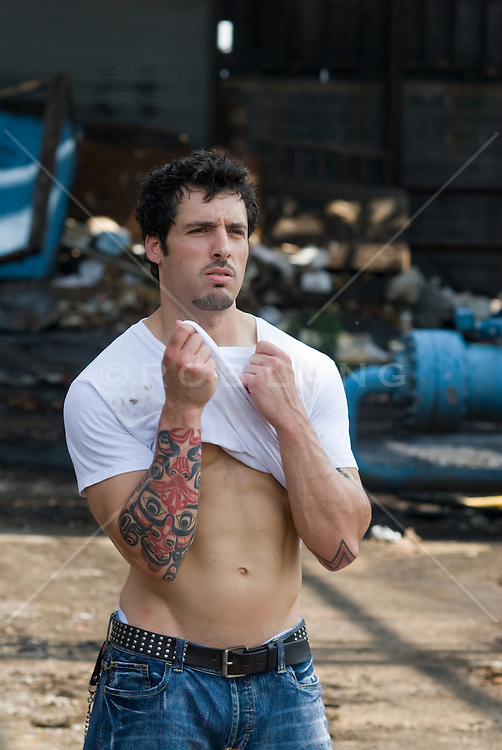 man with tattoed arms in an industrial area lifting his t-shirt