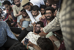 June 17, 2017 - Khudwani, Kashmir, India - Kashmiri villagers touch the face of local rebel Lashkar-e-Taiba (LeT) commander Junaid Matoo during his funeral in Khudwani village about 60 kilometers (37 miles) south of Srinagar. Three militants were killed Saturday in a gun battle with government forces in the disputed region. Two civilians were killed and dozens of others injured in clashes that erupted near the gunfight site, officials said. (Credit Image: © Ahmer Khan/NurPhoto via ZUMA Press)