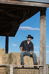 hot cowboy sitting on a hay bale  in a barn