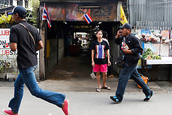© Licensed to London News Pictures. 19/01/2014. Anti-Government protester security guards run in search for the attacker who used a grenade.The grenade attack has reportedly injured 28 people at the protest site at the Victory Monument in Bangkok Thailand. Anti-government protesters launch 'Bangkok Shutdown', blocking major intersections in the heart of the capital, as part of their bid to oust the government of Prime Minister Yingluck Shinawatra ahead of elections scheduled to take place on February 2. Photo credit : Asanka Brendon Ratnayake/LNP