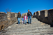 American Chinese family walk the ancient Great Wall of China at Mutianyu, north of Beijing, China
