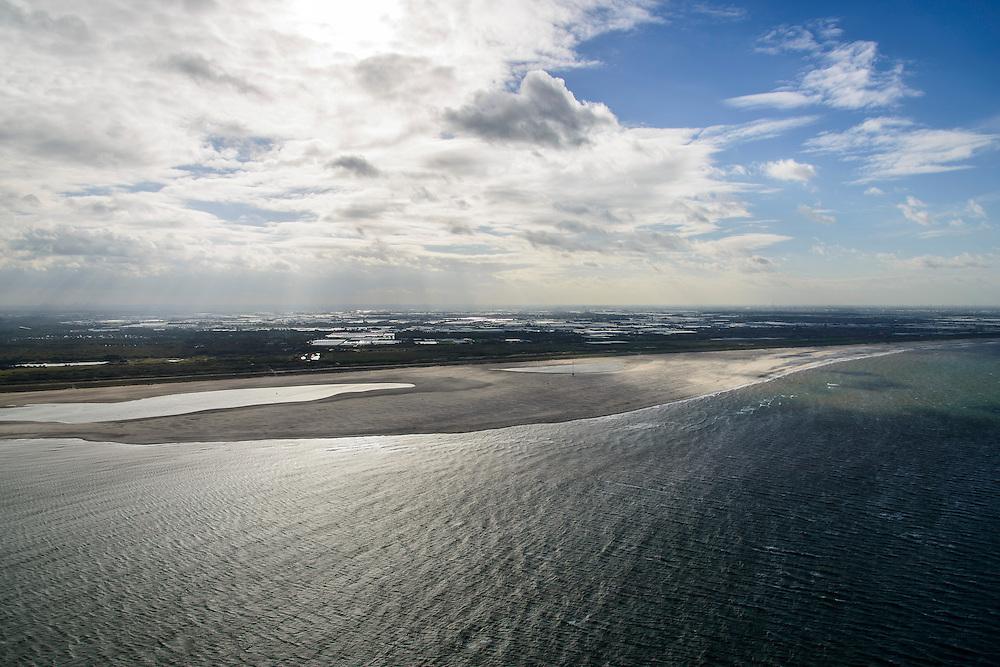 Nederland, Zuid-Holland, Gemeente Westland, 23-10-2013; Delflandse Kust ter hoogte van Ter Heijde en Monster, Westland met kassen aan de horizon. Zandmotor, aanleg van kunstmatig schiereiland door het opspuiten van zand voor de kust. Wind, golven en stroming zullen het zand langs de kust verspreiden waardoor breder stranden en duinen ontstaan. De zandmotor is een experiment in het kader van kustonderhoud en kustverdediging. In de achtergrond de kassen van het Westland.<br /> Sand Engine, construction of artificial peninsula by the raising of sand for the coast of Ter Heijde (near the Hague). Wind, waves and currents will distribute the sand along the coast yielding wider beaches and dunes along the coastline. The Sand Engine is a experiment for coastal maintenance of coastal defense. In the background the Westland greenhouses.<br /> luchtfoto (toeslag op standard tarieven);<br /> aerial photo (additional fee required);<br /> copyright foto/photo Siebe Swart