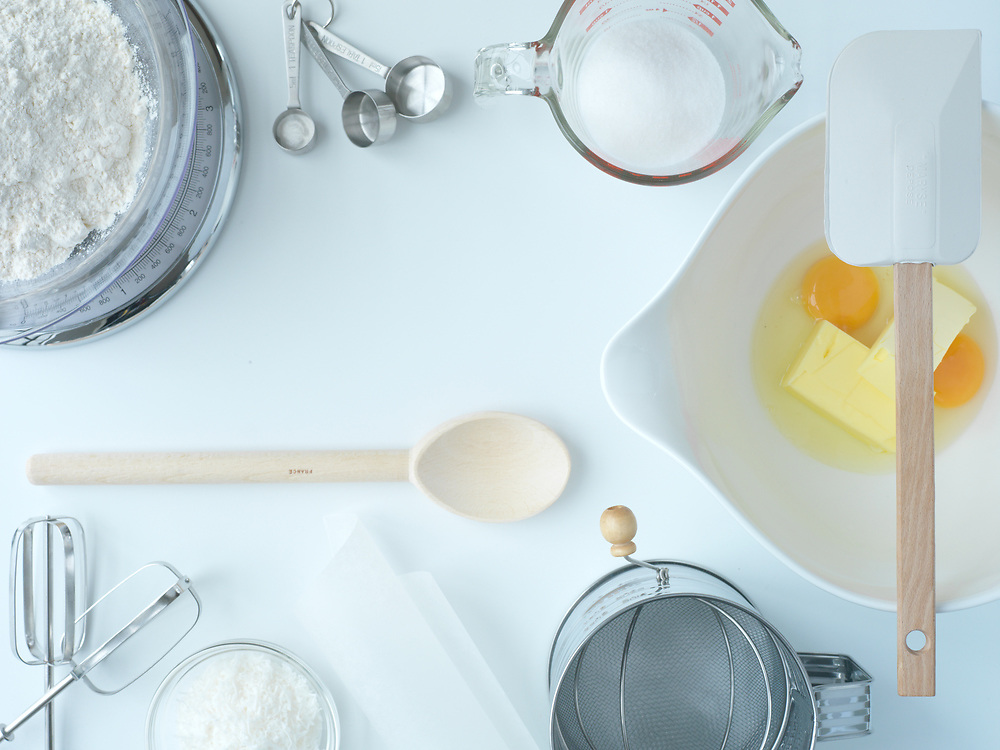 Birds eye view of baking utensils and ingredients on a white background.