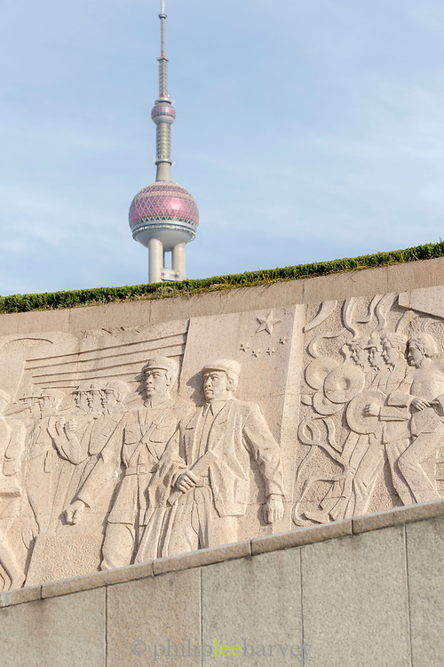 Bas relief with the likenesses of men on the base of Monument to the Peoples Heroes and Oriental Pearl Tower in the background, the Bund, Shanghai, China