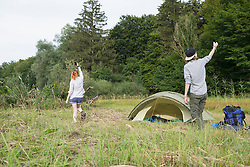 Young couple trying to get mobile coverage in front of camp tent, Bavaria, Germany