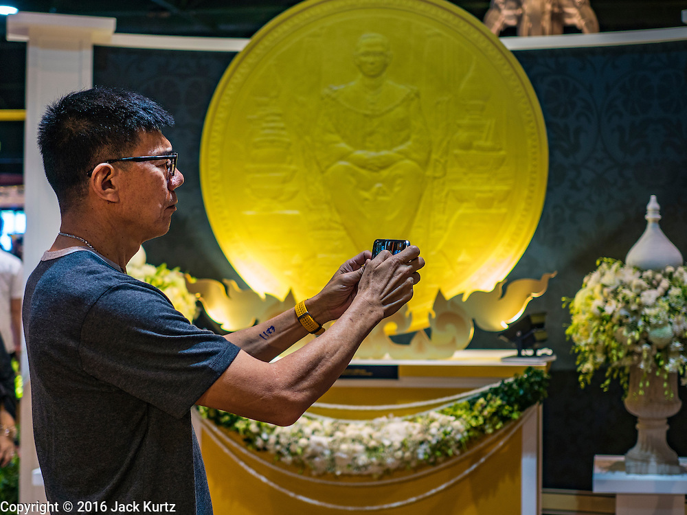 22 DECEMBER 2016 - BANGKOK, THAILAND: A man uses his smart phone to photograph mockups of commemorative coins honoring the late King at Queen Sirikit Convention Center. The Thai treasury department sold commemorative coins to honor Bhumibol Adulyadej, the Late King of Thailand, at Queen Sirikit Convention Center in Bangkok. Thecoins celebrate milestones in the beloved monarch's life. PHOTO BY JACK KURTZ