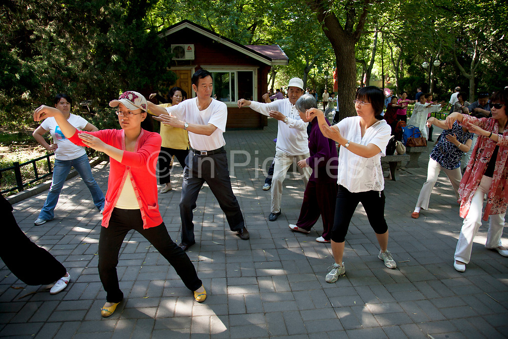 People take their morning tai chi chuan exercise in Zizhuyuan Park in Beijing, China. This park is well known as a place where middle aged or elderly Chinese come. This can take all forms including some surprising ones. Purple Bamboo Park (Zi Zhu Yuan Gongyuan) also called Zizhuyuan Park or Black Bamboo Park largest parks in Beijing. It is located in the Haidian District. The park consist of three connecting lakes covering over a total area of 48 hectares. Typical of the classical Chinese garden style, and like many of Beijing's parks and gardens, it is a mountain-water landscaped garden. Constructed around canals and large lakes, the Bamboo Park is known for its liberal use of verdant bamboo groves. The garden has a variety of bamboos on display. Young people also believe that if they go to the park as a couple that their relationship is doomed to fail.