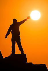 © Licensed to London News Pictures. 17/09/2020. Ilkley UK. A man reaches out to the sun as it rises over the Cow & Calf rocks on Ilkley moor this morning in Yorkshire. Photo credit: Andrew McCaren/LNP