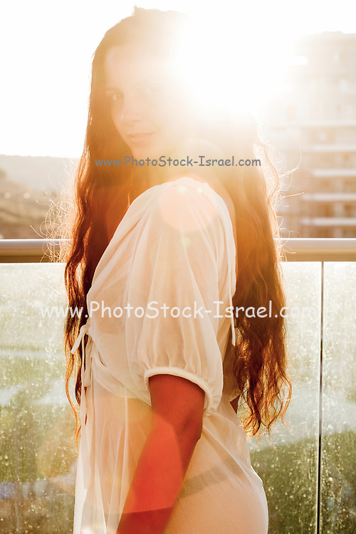 Young confident woman in her 20s with long brown hair in casual white dress. Backlit by the sun. Model release available