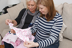 Mother with pregnant daughter looking at baby clothes..