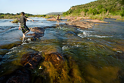 Stock photo of two young children playing on the rocks in the Llano River in the Texas Hill Country