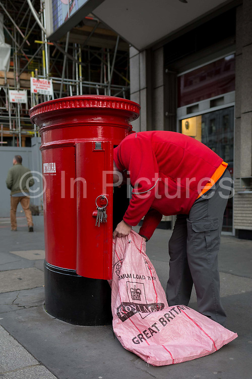 A Royal Mail postal worker leans into a post box to empty a batch of letters and parcels, on 20th November 2019, in the City of London, England.