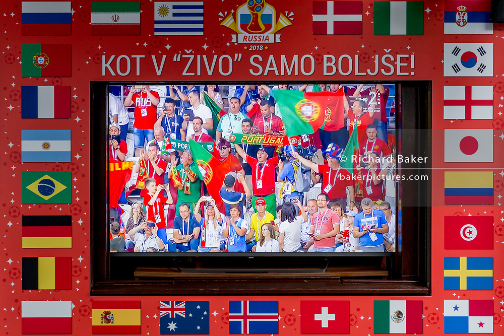 """The Portuguese football fans are shown on a street TV screen bordered by international flags before their game with Spain in the 2018 World Cup in Russia, in the Slovenian capital, Ljubljana, on 25th June 2018, in Ljubljana, Slovenia. Above the screen it reads: """"Just like in the living room just better."""""""