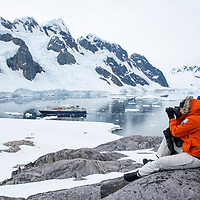 A woman photographs the grandiose landscape from a viewpoint on Booth Island at Port Charcot in Antarctica.