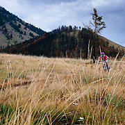 Heather Goodrich rides to the car to escape an oncoming summer thunderstorm in the Tetons near Jackson, Wyoming.