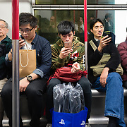People checking smartphones while travelling on a Hong Kong underground train