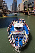 Sightseeing boats along the Chicago River pass under the Lasalle Street Bridge during summer in Chicago, Illinois, USA