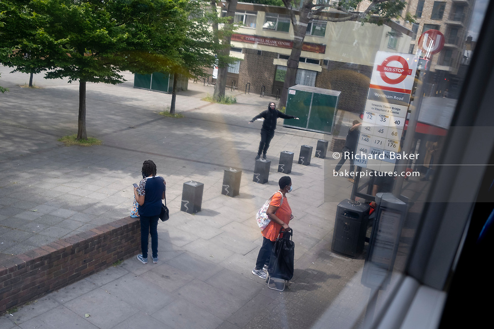 A man wearing a Covid mask, runs towards a waiting bus on the Walworth Road in south London, on 11th June 2021, in London, England.