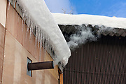 chimney with white smoke and snow on the roof