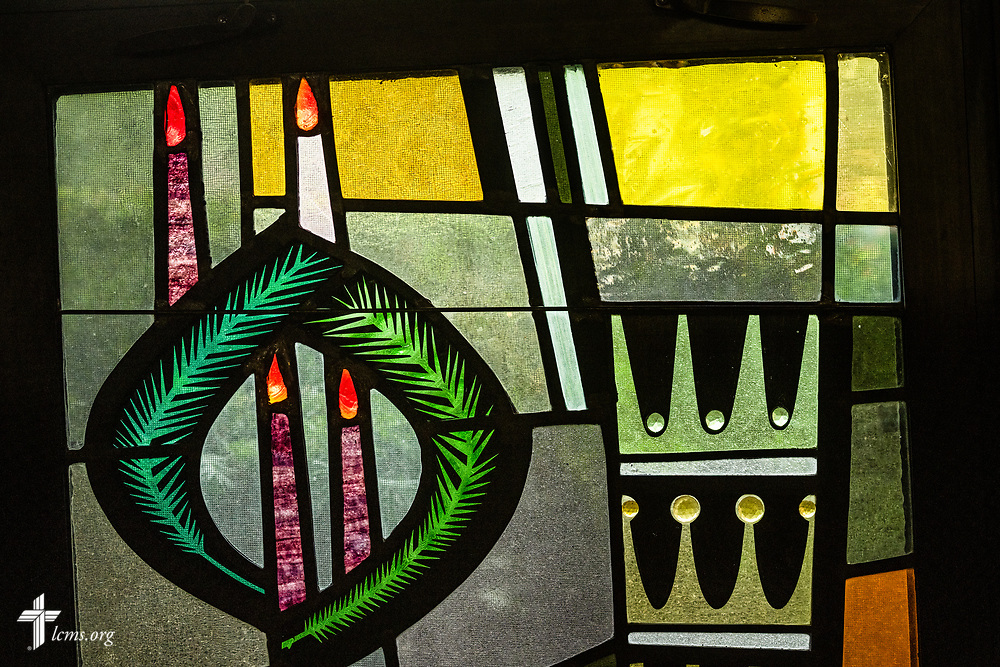 Stained glass depicting Advent with the wreath, candles, and rays from a five-pointed star (not pictured) that reach down to three crowns representing the three kings, on Sunday, Aug. 2, 2020, at Elm Grove Lutheran Church, Elm Grove, Wis. LCMS Communications/Erik M. Lunsford