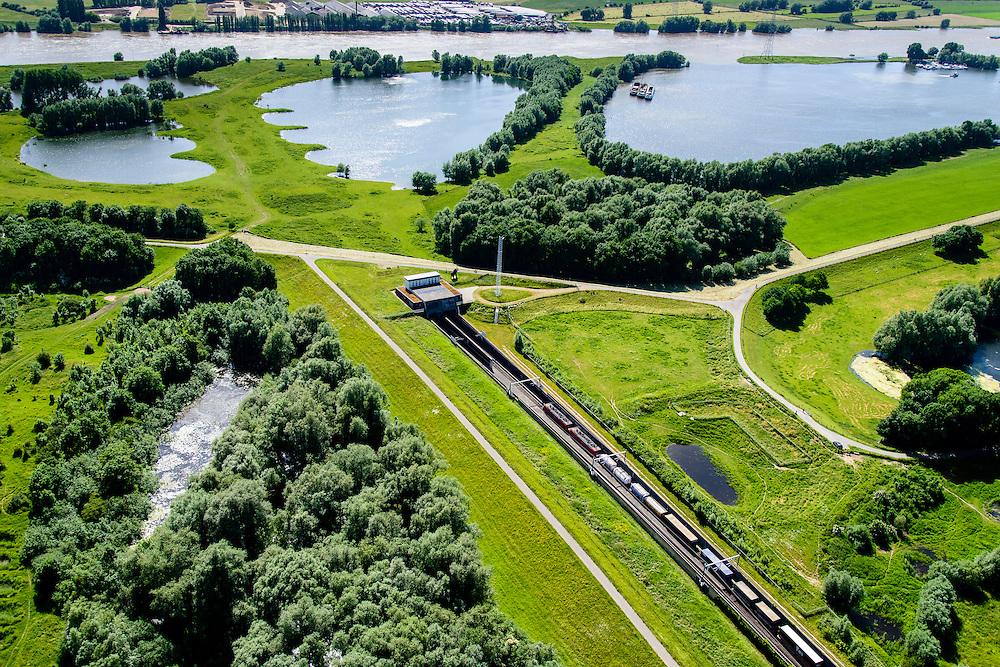 Nederland, Gelderland, Duiven, 09-06-2016; Groessen, natuurgebied Kandia. Goederentrein op Betuweroute nadert de tunnel onder Pannerdens kanaal. Dienstgebouw van de tunnel onder het Pannerdensch kanaal, in westelijke richting, Neder-Rijn in de achtergrond.<br /> Tunnel Betuweroute, freight railway, Pannerdensch channel (Lower Rhine) on the horizon.<br /> <br /> luchtfoto (toeslag op standard tarieven);<br /> aerial photo (additional fee required);<br /> copyright foto/photo Siebe Swart