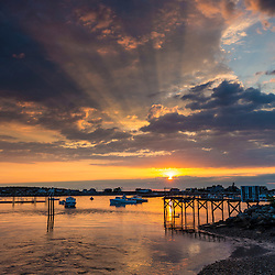 Sun rays shoot through the clouds above Rye Harbor, in Rye, New Hampshire.