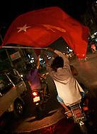 A motorbike passenger waves a NLD flag at night in Mandalay. Myanmar. 2012