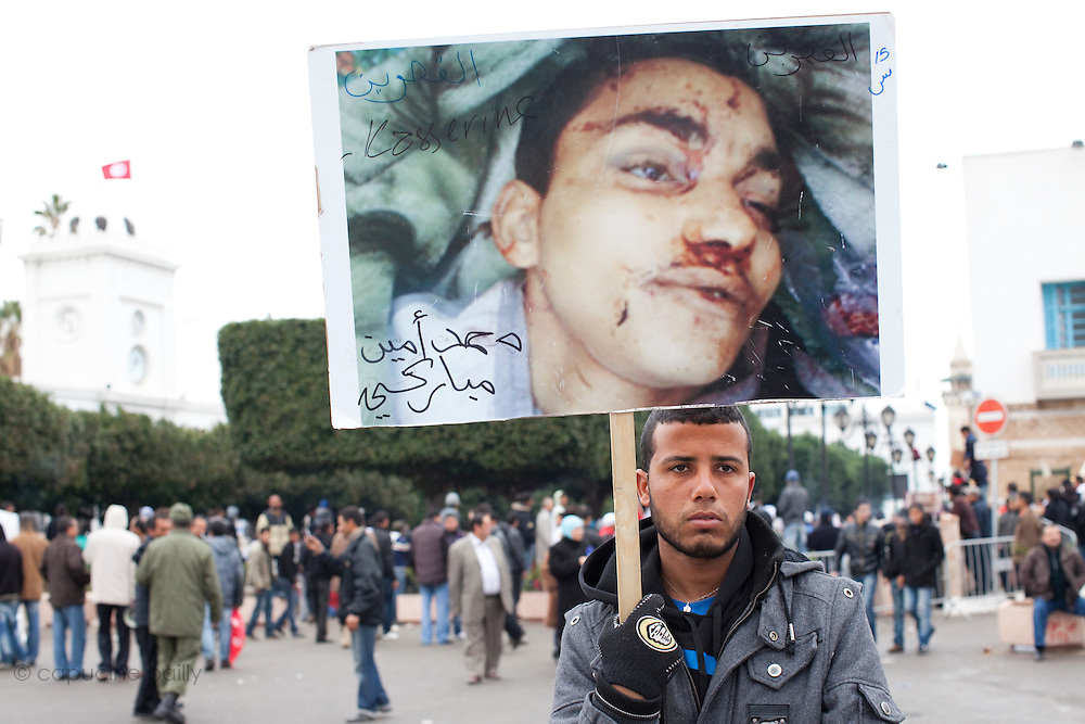 Tunis, Tunisia. January 25th 2011.At the entrance of the Kasbah square, a young man shows people the picture of his killed younger brother during the deadly riots twelve days ago......