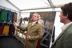 © Licensed to London News Pictures. 31/07/2015. Leeds , UK . NIGEL FARAGE tries on a jacket at the Ratcatcher marquee at the CLA GameFair ( Country Landowners Association ) at Harewood House in Yorkshire . Photo credit: Joel Goodman/LNP