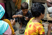 A family is decorating glass bracelets in front of their home transformed into a small-scale workshop in the slum surrounding Firozabad, renowned as the 'glass city', in Uttar Pradesh, northern India. Due to extreme poverty, over 20.000 young children are employed to complete the bracelets produced in the industrial units. This area is considered to be one of the highest concentrations of child labour on the planet. Forced to work to support their disadvantaged families, children as young as five are paid between 30-40 Indian Rupees (approx. 0.50 EUR) for eight or more hours of work daily. Most of these children are not able to receive an education and are easily prey of the labour-poverty cycle which has already enslaved their families to a life of exploitation. Children have to sit in crouched positions, use solvents, glues, kerosene and various other dangerous materials while breathing toxic fumes and spending most time of the day in dark, harmful environments. As for India's Child Labour Act of 1986, children under 14 are banned from working in industries deemed 'hazardous' but the rules are widely flouted, and prosecutions, when they happen at all, get bogged down in courts for lengthy periods. A ban on child labour without creating alternative opportunities for the local population is the central problem to the Indian Government's approach to the social issue affecting over 50 million children nationwide.
