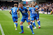 Peterborough United defender Jason Naismith (2) picks up a sweet that was thrown by the Luton fans as Posh celebrated their first goal during the EFL Sky Bet League 1 match between Peterborough United and Luton Town at London Road, Peterborough, England on 18 August 2018.
