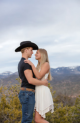 cowboy with a blond girl outdoors on a mountain range