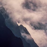 Clouds swirl up against giant Himalayn mountains the gorge of the Dudh Kosi River, Khumbu region, Nepal.