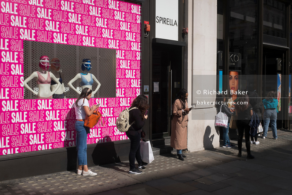With a further 89 UK covid victims in the last 24hrs, bringing the total victims to 43,995 during the Coronavirus pandemic, shops continue opening along London's Regent Street where shoppers queue for the Sales leaving 2 metre intervals, on 2nd July 2020, in London, England.