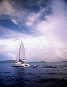 A sailboat cruises through carribean waters as it nears sunset