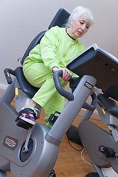 Older woman working out on exercise bikes at a gym,