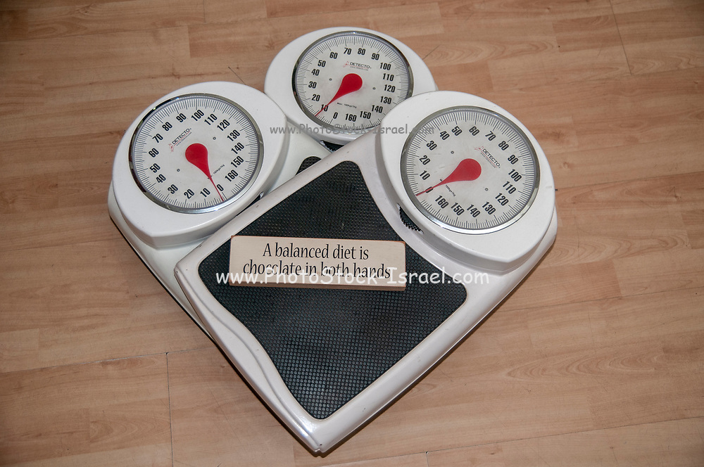 A balanced diet is a chocolate in each hand. Dieting, weight loss and body image conceptual image of three analogue scales stacked one on top of the other