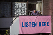 A resident of Bowater House on the Golden Lane Estate with a banner on the balcony protesting about the 10-storey luxury apartment development called The Denizen, a controversial building by Taylor Wimpey that locals say will dominate their view and block their daylight, on 30th October 2017, in London, England. Residents on the Estate have erected banners by artists Jeremy Deller and Elizabeth Price to picket the developers. Despite this, Wimpey say, We are one of the UKs largest residential developers. As a responsible developer we are committed to working with local people and communities.