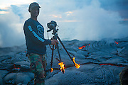 """photographer Kawika Singson with his shoes and tripod in flames due to the intense heat of lava.<br /><br />Singson is an extreme hiker and landscape photographer based in Kailua-Kona, Hawaii. Over the years, he has photographed in countless locations all over the Big Island, often in locations that the <br /><br />general public would find very difficult to get to. He """"has taken many risks to capture just the right shot to share with the rest of the world,"""" he says.<br /><br />The photograph above was shot last week on July 4th, 2013. When we asked Singson about the location, he wouldn't reveal anything aside from the fact that it was in Hawaii. """"I don't like giving out my locations,"""" he said. """"It's a secret. Plus, I don't want people to go there and get hurt.""""<br /><br />It may look too crazy to be true, but Singson insists that it's a genuine photograph: """"That's real lava real flames and it was really hot! I could stand the heat only for a few seconds.""""<br />Singson says that this is the first time he has had his clothing and/or equipment catch on fire while photographing near lava. His shoes have started smoking before, but he had never seen flames.<br />It should go without saying, but you shouldn't try this stunt at the volcano near your home. It's incredibly dangerous due to the fact that it's possible to fall through the thin layer of rock into the molten lava below, just like one would fall through ice on a frozen lake. Singson tells us that """"there was only a thin layer of solid rock on top of the magma"""" where he was standing.<br />©Chris Hirata/Exclusivepix"""