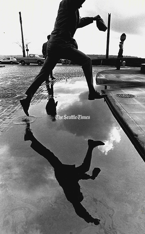 Miniature lake at Pike Place and Virginia Street invited athletic types to leap, while the cautious walked around. (Peter Liddell / The Seattle Times, 1988)