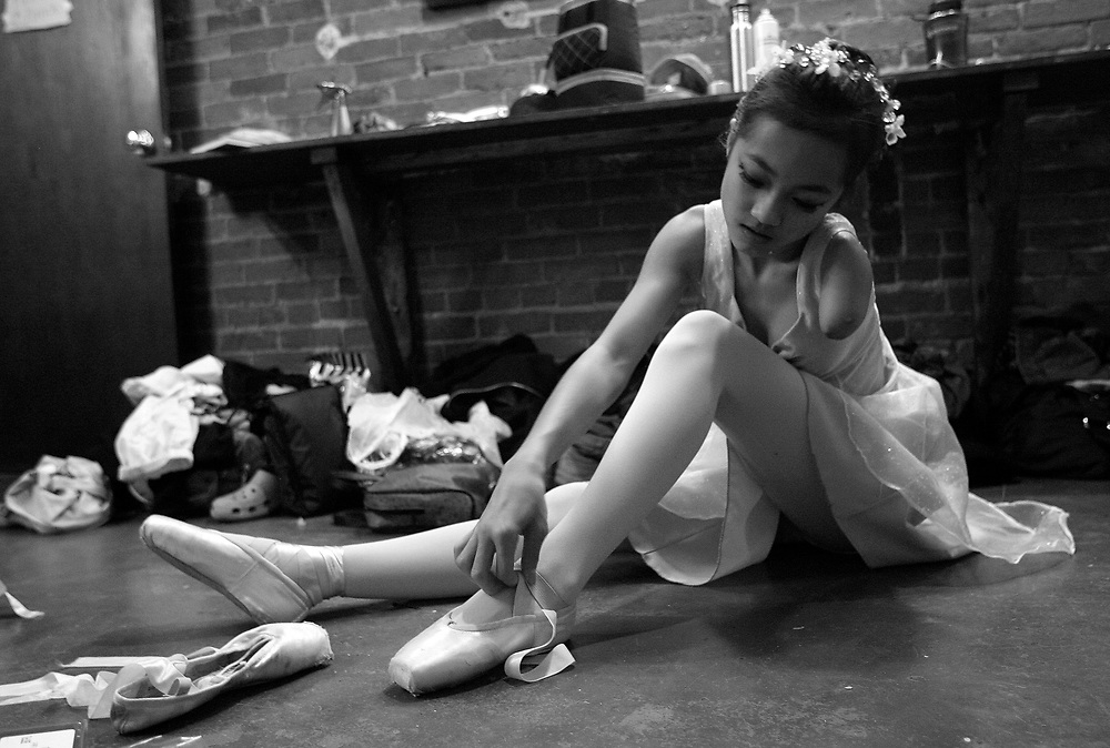 04/03/2009 Northhampton, MA-  Lani Dickinson, 14, puts on her point shoes for Pioneer Valley Ballet's production of Beauty and the Beast.  Lani was born in China with a congenital defect and adopted by an American family.  Despite her disability, she trains hard as a ballerina and would like to someday be a professional dancer.