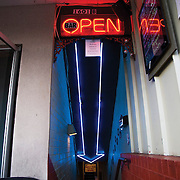 A blue neon arrow illuminates the stairwell that leads to Jeff's Bucket Shop in the Montford neighborhood of Charlotte, NC.