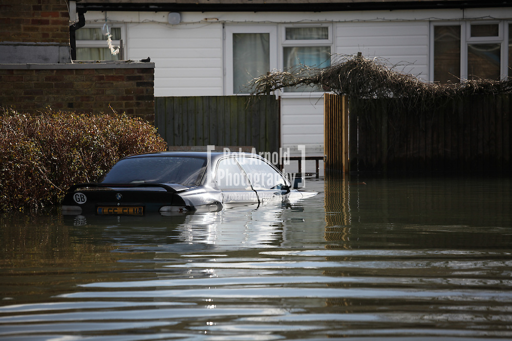 22/02/2014. Basingstoke, Hampshire. A car surrounded by flood water on Grampian Way, in the Buckskin area of Basingstoke, Hampshire. Groundwater levels are continuing to rise in the area, forcing 69 homes to be evacuated in the Buckskin Area of the commuter town. Photo credit : Rob Arnold