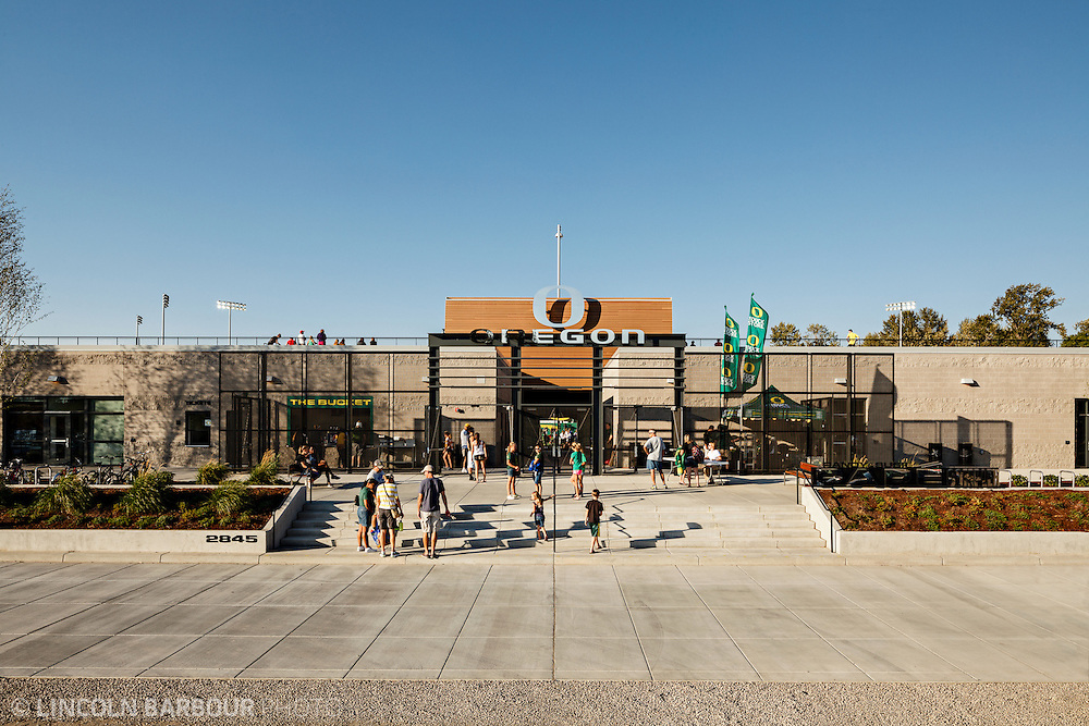 Architectural photo of University of Oregon's Women's Soccer & Lacrosse Stadium. Designed by DLR Group. A graphic view of the front entrance with fans starting to filter in. Blue skies with no clouds overhead.