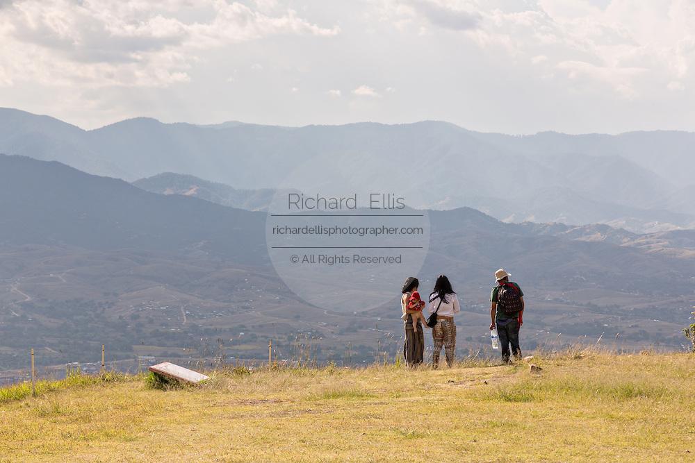 Tourists view the Valley of Oaxaca from Monte Albán pre-Columbian archaeological site in the Santa Cruz Xoxocotlán, Oaxaca, Mexico.
