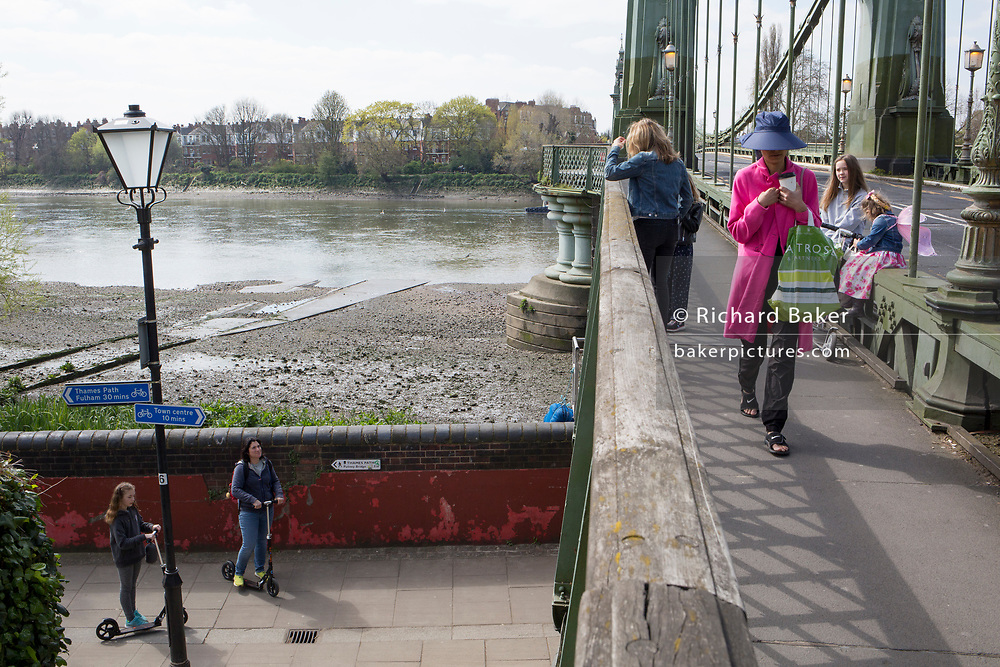 """After being closed indefinitely to all traffic due to structural faults, pedestrians walk across Hammersmith Bridge, on 11th April 2019, in west London, England. Safety checks revealed """"critical faults"""" and Hammersmith and Fulham Council has said it's ben left with no choice but to shut the bridge until refurbishment costs could be met. The government has said that between 2015 and 2021 its is providing £11bn of support to the 132-year-old bridge."""